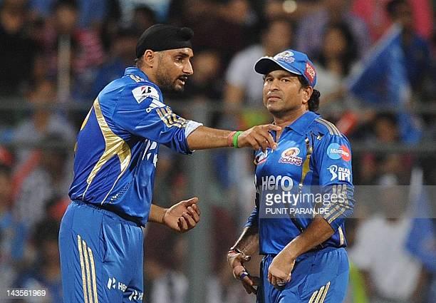 Mumbai Indians captain Harbhajan Singh speaks with team mate Sachin Tendulkar during the IPL Twenty20 cricket match between Mumbai Indians and Deccan...