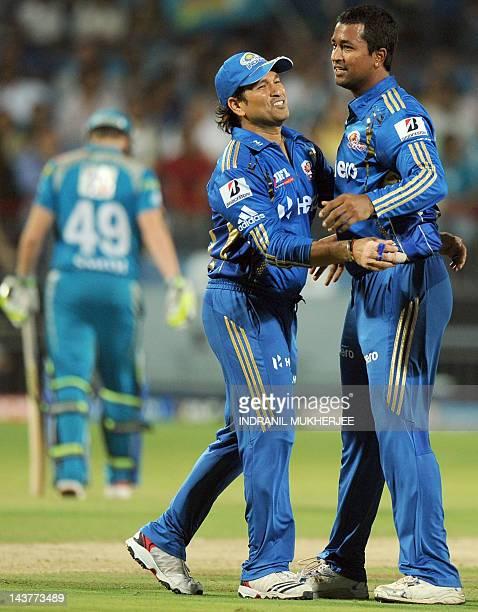 Mumbai Indians' cricketer Sachin Tendulkar congratulates bowler Pragyan Ojha after taking the wicket of Pune Warriors India's batsman Steve Smith...