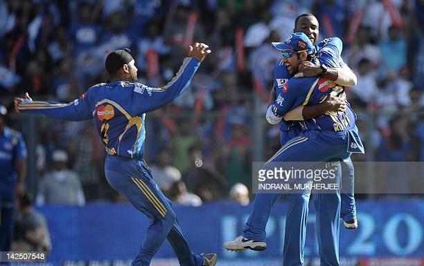 Mumbai Indians cricketers Harbhajan Singh Kieron Pollard and Rohit Sharma celebrate the wicket of Pune Warriors India batsman Callum Ferguson during...