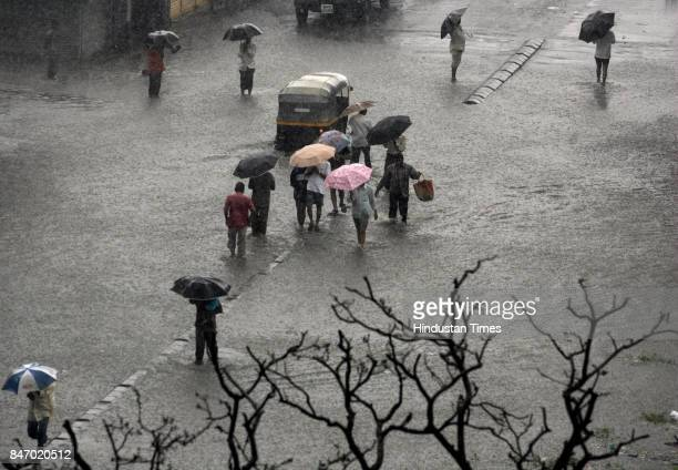 Mumbai Monsoon Commuters had to use the road dividers as Dairy Road at Nehru Nagar in Kurla submerged under water after heavy rains continued to lash...