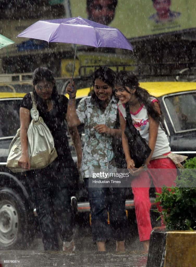 Young college girls with unmbrella tries to save themselves and their bags from the sudden shower outside N.M. College on Thursday.