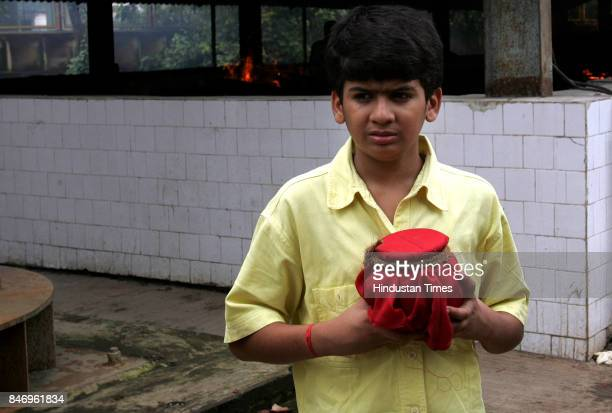 Jitendra Davey carrying the ashes of his father Govindji Davey who was one of the victims of the serial train bomb blasts at Oshiwara crematorium