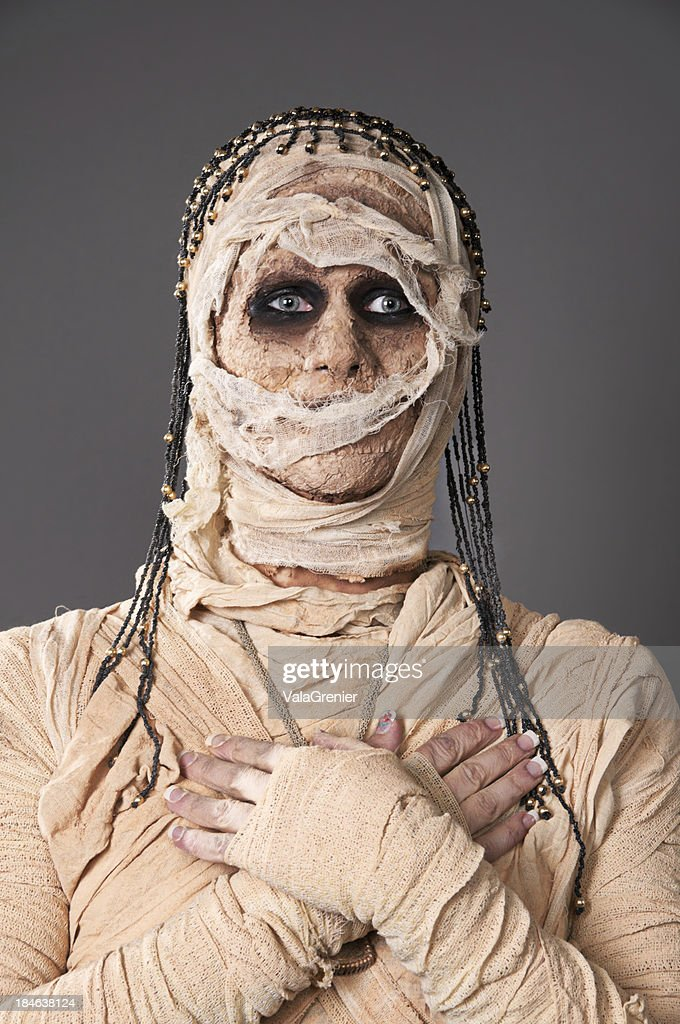 Mummy with hands crossed staring at camera.