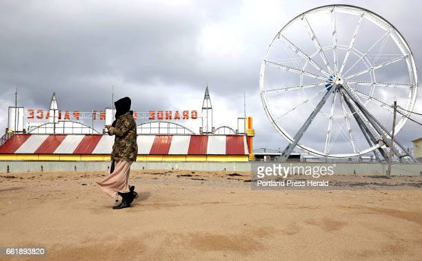 Muna Omar of Portland checks photos on her cellphone during a stroll on Old Orchard Beach