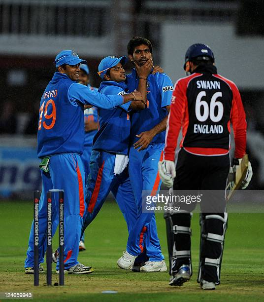 Munaf Patel of India celebrates with team mates Suresh Raina and Rahul Dravid after a direct hit to run out Graeme Swann of England during the 4th...