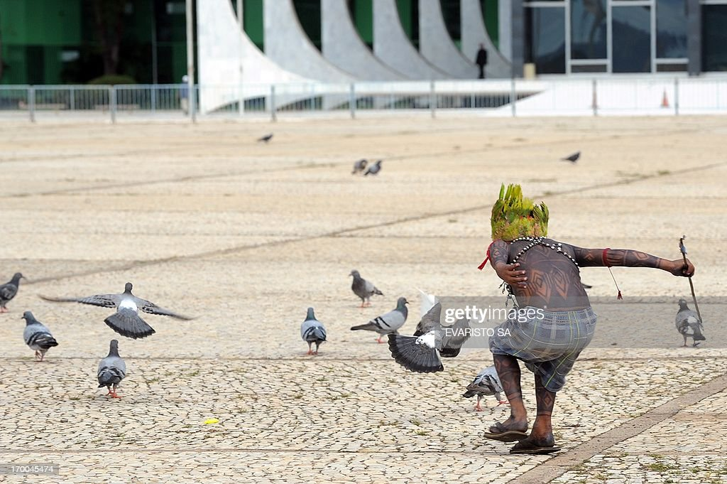 A Munduruku indigenous child runs after pigeons during a protest in front of the Planalto Palace in Brasilia, on June 6, 2013. Five indigenous tribes are calling for legislation under which they would have to be consulted prior to any official decision affecting them with respect to the dam's construction. Belo Monte, which is being built at a cost of $13 billion, is expected to flood an area of 500 square km along the Xingu River, displacing 16,000 people, according to the government. Some NGOs have estimated that some 40,000 people would be displaced by the massive project. Indigenous groups say the dam will harm their way of life while environmentalists warn of deforestation, greenhouse gas emissions and irreparable damage to the ecosystem. AFP PHOTO / Evaristo SA