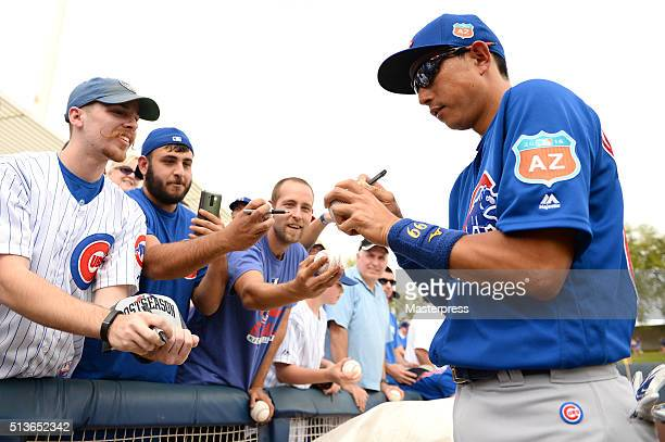 Munenori Kawasaki of Chicago Cubs signs autographs for fans before the spring training game between Milwaukee Brewers and Chicago Cubs at Maryvale...
