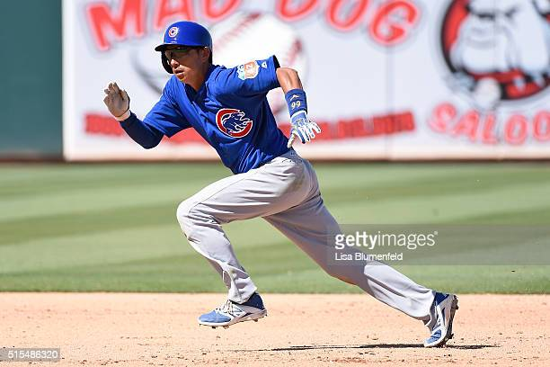 Munenori Kawasaki of the Chicago Cubs runs safely to third base in the fifth inning against the Oakland Athletics on March 13 2016 in Mesa Arizona