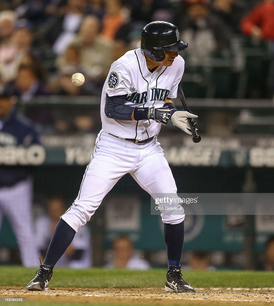 <a gi-track='captionPersonalityLinkClicked' href=/galleries/search?phrase=Munenori+Kawasaki&family=editorial&specificpeople=690355 ng-click='$event.stopPropagation()'>Munenori Kawasaki</a> #61 of the Seattle Mariners grimaces as he is hit with a pitch against the Los Angeles Angels of Anaheim at Safeco Field on October 2, 2012 in Seattle, Washington.