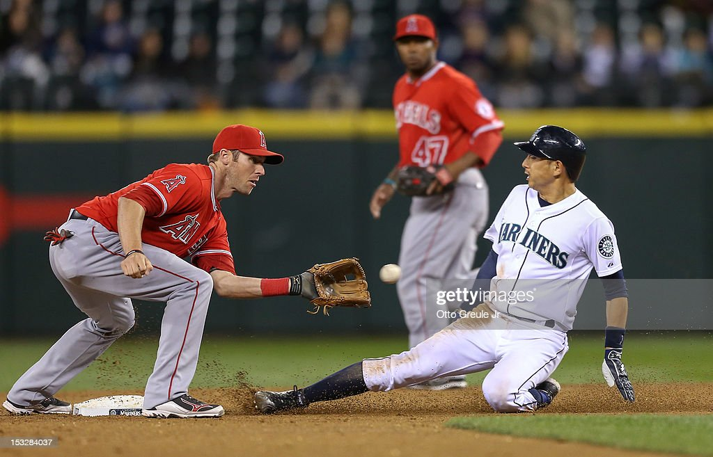 <a gi-track='captionPersonalityLinkClicked' href=/galleries/search?phrase=Munenori+Kawasaki&family=editorial&specificpeople=690355 ng-click='$event.stopPropagation()'>Munenori Kawasaki</a> #61 of the Seattle Mariners steals second base against shortstop <a gi-track='captionPersonalityLinkClicked' href=/galleries/search?phrase=Andrew+Romine&family=editorial&specificpeople=2338123 ng-click='$event.stopPropagation()'>Andrew Romine</a> #18 of the Los Angeles Angels of Anaheim at Safeco Field on October 2, 2012 in Seattle, Washington.