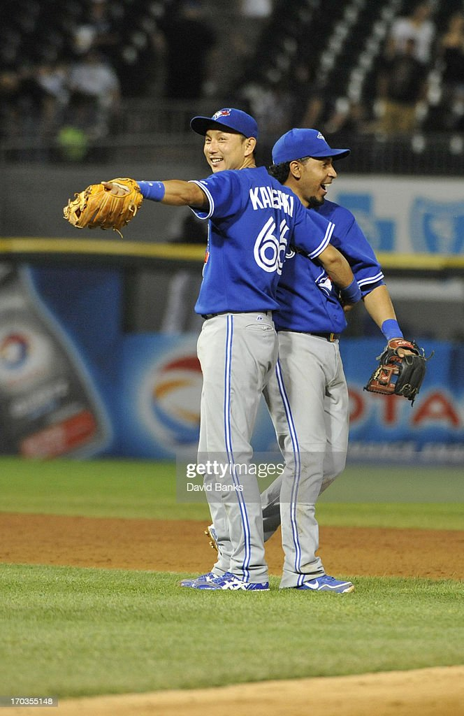 <a gi-track='captionPersonalityLinkClicked' href=/galleries/search?phrase=Munenori+Kawasaki&family=editorial&specificpeople=690355 ng-click='$event.stopPropagation()'>Munenori Kawasaki</a> #66 of the Toronto Blue Jays and <a gi-track='captionPersonalityLinkClicked' href=/galleries/search?phrase=Maicer+Izturis&family=editorial&specificpeople=239100 ng-click='$event.stopPropagation()'>Maicer Izturis</a> #3 celebrate their 7-5 win in ten innings against the Chicago White Sox on June 11, 2013 at U.S. Cellular Field in Chicago, Illinois.