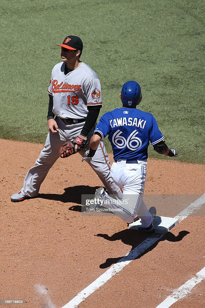 Munenori Kawasaki of the Toronto Blue Jays arrives at first base after hitting a bunt single in the third inning during MLB game action against the...