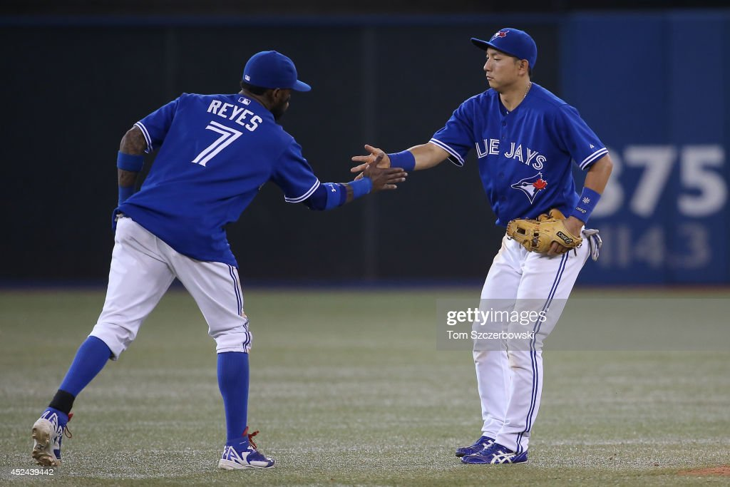 <a gi-track='captionPersonalityLinkClicked' href=/galleries/search?phrase=Munenori+Kawasaki&family=editorial&specificpeople=690355 ng-click='$event.stopPropagation()'>Munenori Kawasaki</a> #66 of the Toronto Blue Jays celebrates their victory with Jose Reyes #7 during MLB game action against the Texas Rangers on July 20, 2014 at Rogers Centre in Toronto, Ontario, Canada.