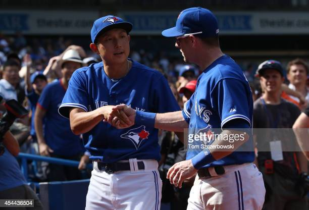Munenori Kawasaki of the Toronto Blue Jays celebrates their victory with Steve Tolleson during MLB game action against the New York Yankees on August...