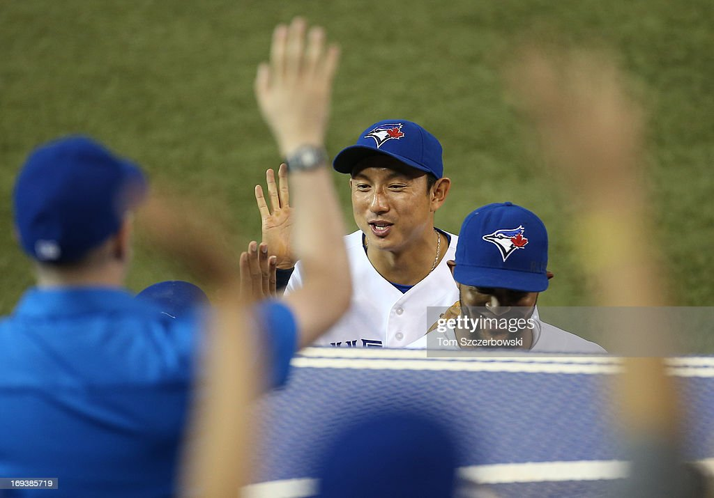 Munenori Kawasaki #66 of the Toronto Blue Jays celebrates with Emilio Bonifacio #1 (R) after they turned an inning-ending double play in the first inning during MLB game action against the Baltimore Orioles on May 23, 2013 at Rogers Centre in Toronto, Ontario, Canada.