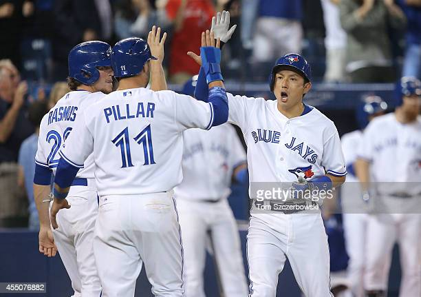 Munenori Kawasaki of the Toronto Blue Jays celebrates with Kevin Pillar and Colby Rasmus after they all scored on a basesclearing double in the...