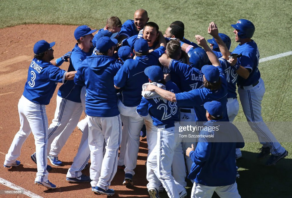 <a gi-track='captionPersonalityLinkClicked' href=/galleries/search?phrase=Munenori+Kawasaki&family=editorial&specificpeople=690355 ng-click='$event.stopPropagation()'>Munenori Kawasaki</a> #66 of the Toronto Blue Jays celebrates with teammates after driving in the winning runs in the ninth inning during MLB game action against the Baltimore Orioles on May 26, 2013 at Rogers Centre in Toronto, Ontario, Canada.