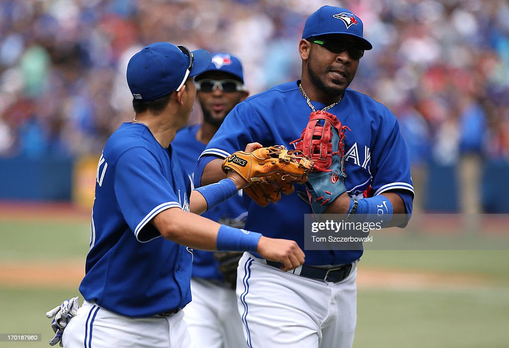 <a gi-track='captionPersonalityLinkClicked' href=/galleries/search?phrase=Munenori+Kawasaki&family=editorial&specificpeople=690355 ng-click='$event.stopPropagation()'>Munenori Kawasaki</a> #66 of the Toronto Blue Jays congratulates <a gi-track='captionPersonalityLinkClicked' href=/galleries/search?phrase=Edwin+Encarnacion&family=editorial&specificpeople=598285 ng-click='$event.stopPropagation()'>Edwin Encarnacion</a> #10 after making a play to end the eighth inning against the Texas Rangers during MLB game action on June 8, 2013 at Rogers Centre in Toronto, Ontario, Canada.