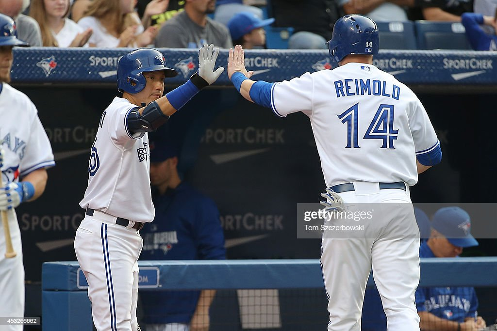 Munenori Kawasaki #66 of the Toronto Blue Jays congratulates Nolan Reimold #14 after Reimold scored a run in the first inning during MLB game action against the Baltimore Orioles on August 6, 2014 at Rogers Centre in Toronto, Ontario, Canada.