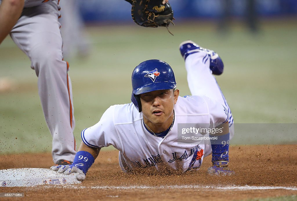 <a gi-track='captionPersonalityLinkClicked' href=/galleries/search?phrase=Munenori+Kawasaki&family=editorial&specificpeople=690355 ng-click='$event.stopPropagation()'>Munenori Kawasaki</a> #66 of the Toronto Blue Jays dives back safely to first base on a pick-off attempt in the eighth inning during MLB game action against the Baltimore Orioles on August 6, 2014 at Rogers Centre in Toronto, Ontario, Canada.