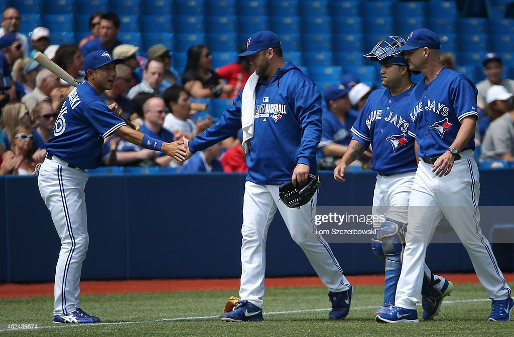 <a gi-track='captionPersonalityLinkClicked' href=/galleries/search?phrase=Munenori+Kawasaki&family=editorial&specificpeople=690355 ng-click='$event.stopPropagation()'>Munenori Kawasaki</a> #66 of the Toronto Blue Jays gives encouragement to <a gi-track='captionPersonalityLinkClicked' href=/galleries/search?phrase=Mark+Buehrle&family=editorial&specificpeople=204644 ng-click='$event.stopPropagation()'>Mark Buehrle</a> #56 as he makes his way from the bullpen to the dugout before the start of MLB game action against the Texas Rangers on July 20, 2014 at Rogers Centre in Toronto, Ontario, Canada.