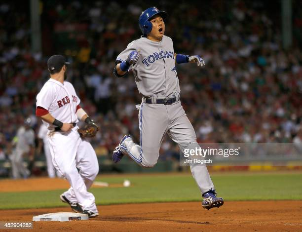 Munenori Kawasaki of the Toronto Blue Jays reacts after his successful sacrifice bunt as Dustin Pedroia of the Boston Red Sox makes the out at first...