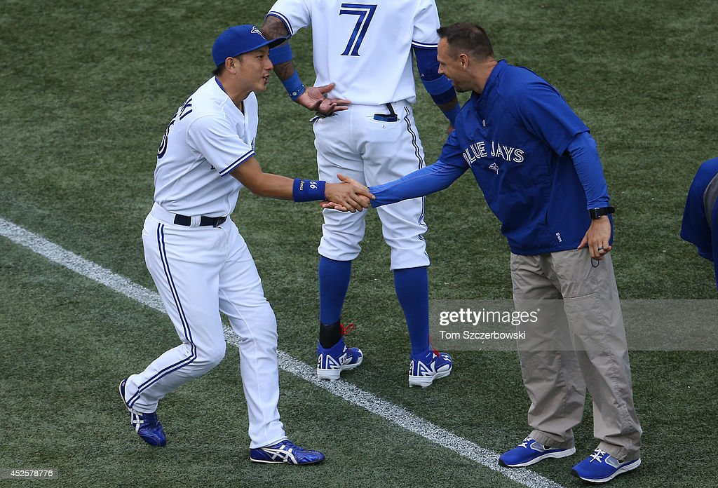 <a gi-track='captionPersonalityLinkClicked' href=/galleries/search?phrase=Munenori+Kawasaki&family=editorial&specificpeople=690355 ng-click='$event.stopPropagation()'>Munenori Kawasaki</a> #66 of the Toronto Blue Jays shakes hands with a trainer before the start of MLB game action against the Boston Red Sox on July 23, 2014 at Rogers Centre in Toronto, Ontario, Canada.