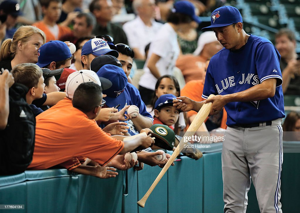 Munenori Kawasaki #66 of the Toronto Blue Jays signs autographs for fans before the game against the Houston Astros at Minute Maid Park on August 24, 2013 in Houston, Texas.