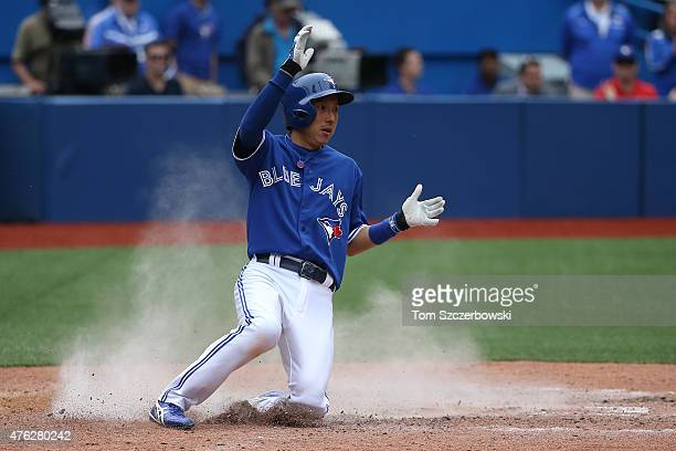 Munenori Kawasaki of the Toronto Blue Jays slides across home plate to score a run on an RBI single by Jose Reyes in the ninth inning during MLB game...
