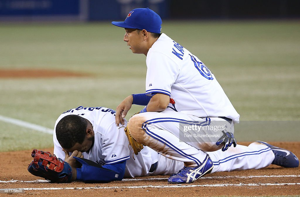 <a gi-track='captionPersonalityLinkClicked' href=/galleries/search?phrase=Munenori+Kawasaki&family=editorial&specificpeople=690355 ng-click='$event.stopPropagation()'>Munenori Kawasaki</a> #66 of the Toronto Blue Jays tends to <a gi-track='captionPersonalityLinkClicked' href=/galleries/search?phrase=Edwin+Encarnacion&family=editorial&specificpeople=598285 ng-click='$event.stopPropagation()'>Edwin Encarnacion</a> #10 after Encarnacion tooka ball to the face on a throwing error by Jose Reyes in the seventh inning during MLB game action against the New York Yankees on June 24, 2014 at Rogers Centre in Toronto, Ontario, Canada.