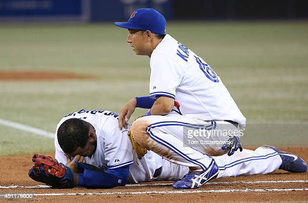 Munenori Kawasaki of the Toronto Blue Jays tends to Edwin Encarnacion after Encarnacion tooka ball to the face on a throwing error by Jose Reyes in...