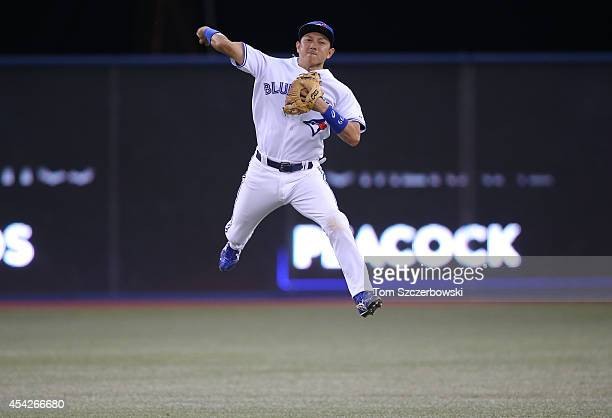 Munenori Kawasaki of the Toronto Blue Jays throws out the baserunner from deep in the hole in the fourth inning during MLB game action against the...