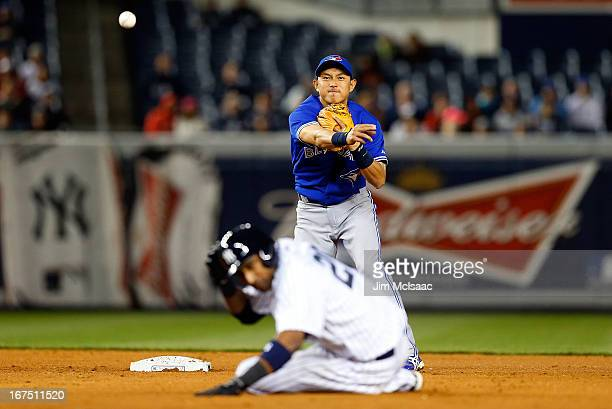 Munenori Kawasaki of the Toronto Blue Jays throws to first base to complete an eighth inning ending double play after forcing out Eduardo Nunez of...