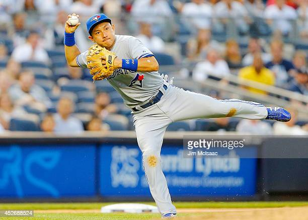 Munenori Kawasaki of the Toronto Blue Jays tries to throw out Brian Roberts of the New York Yankees during the second inning at Yankee Stadium on...