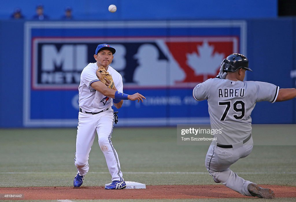 Munenori Kawasaki of the Toronto Blue Jays turns a double play in the second inning during MLB game action as Jose Abreu of the Chicago White Sox...