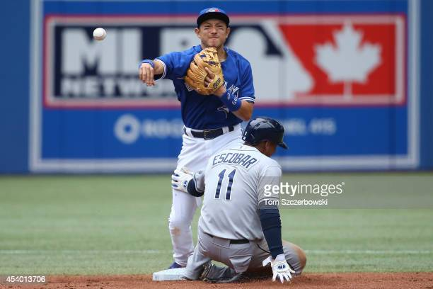 Munenori Kawasaki of the Toronto Blue Jays turns a double play in the third inning during MLB game action as Yunel Escobar of the Tampa Bay Rays...