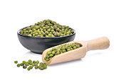 mung beans in wooden scoop and black bowl isolated on white background