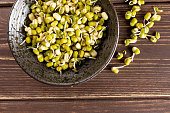 Lot of whole fresh green bean sprouts mungo in a grey ceramic bowl flatlay on brown wood