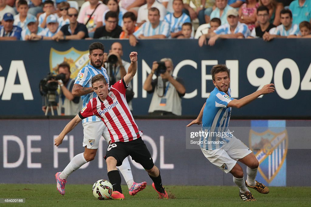 Muniain (C) of Athletic Club Bilbao controls the ball against Samuel (L) and Ignacio Camacho (R) of Malaga CF during the La Liga match between Malaga CF and Athletic Club Bilbao at La Rosaleda Stadium on August 23, 2014 in Malaga, Spain.