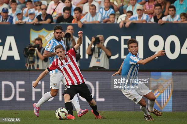 Muniain of Athletic Club Bilbao controls the ball against Samuel and Ignacio Camacho of Malaga CF during the La Liga match between Malaga CF and...
