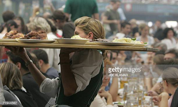 A waitress carrys food on a tray while walking through an overcrowded beer tent on Munich's Oktoberfest beer festival fairgrounds 16 September 2006...