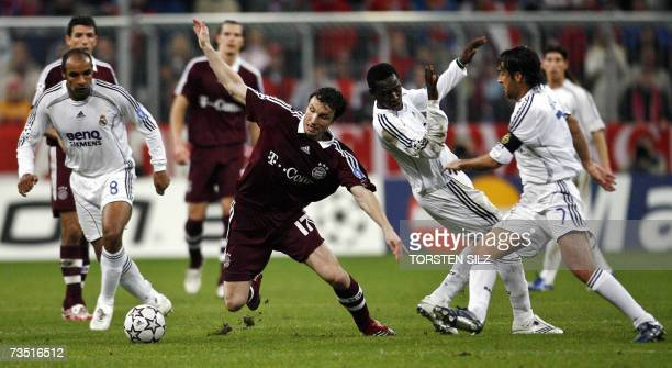 Bayern Munich's Dutch midfielder Mark van Bommel vies with Real Madrid's Brazilian midfielder Emerson Malian Mahamadou Diarra and Dutch striker Ruud...