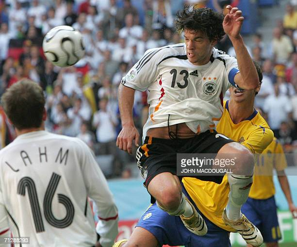 German midfielder Michael Ballack jumps up for the ball as German defender Philipp Lahm looks on during the round of 16 World Cup football match...
