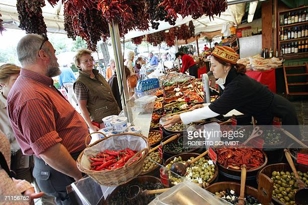 Visitors look at a host of wonderful food on offer in the Viktualienmarkt area of downtown Munich 08 June 2006 one day ahead of the city's hosting of...