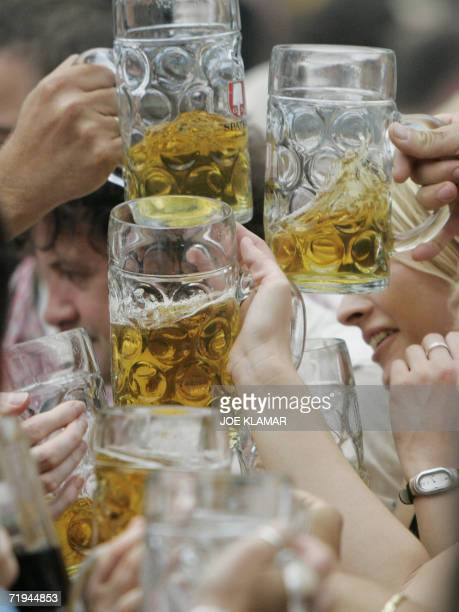 Visitors of the Oktoberfest beer festival clink their glasses of beer known as mass on the opening day of Munich's traditional Oktoberfest beer...