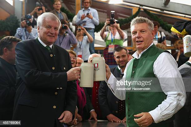 Munich new Mayor Dieter Reiter clink the first beer mugs with Bavarian Governor Horst Seehofer after taping the first Oktoberfest beer barrel at...