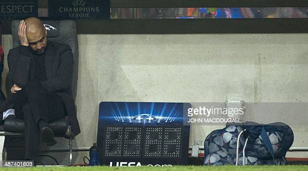 Munich's coach Pep Guardiola of Spain holds his head at the end of the UEFA Champions League secondleg semifinal football match FC Bayern Munich vs...