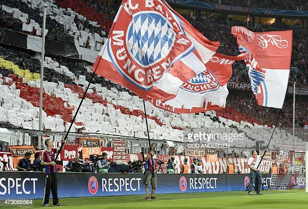 Munich's fans hold their team's flags before the UEFA Champions League football match semi final FC Bayern Munich vs FC Barcelona in Munich on May 12...