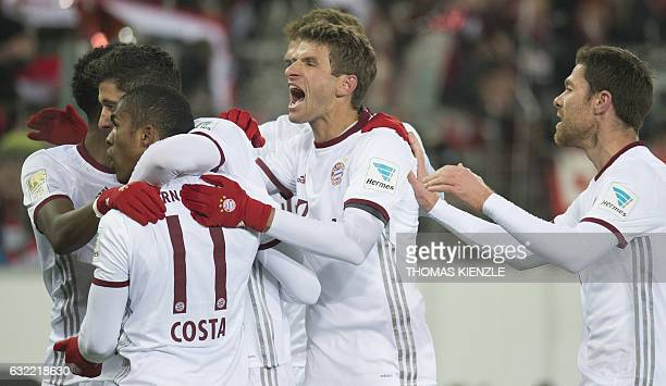 Munich's forward Thomas Mueller celebrates with teammates after they scored during the German first division Bundesliga football match SC Freiburg vs...