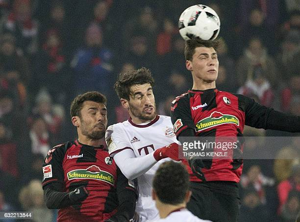 Munich's Spanish midfielder Javier Martinez vies for the ball with Freiburg's defender Pascal Stenzel and midfielder Mike Frantz during the German...